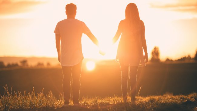 Couple holding hands at dusk